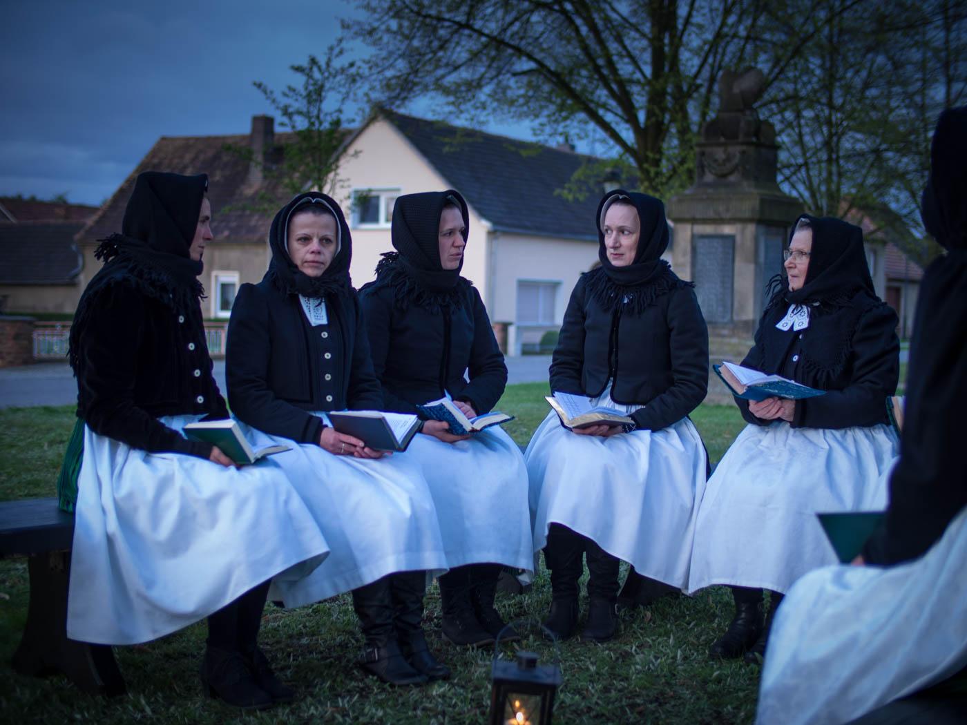 Fünf Uhr früh am Morgen, kurz vor Sonnenaufgang, sammeln sie sich an der Schleifer Kirche: Frauen und Mädchen in sorbischer evangelischer Schleifer Halbtrauertracht.
